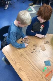 5th graders making cup holders with 1st graders