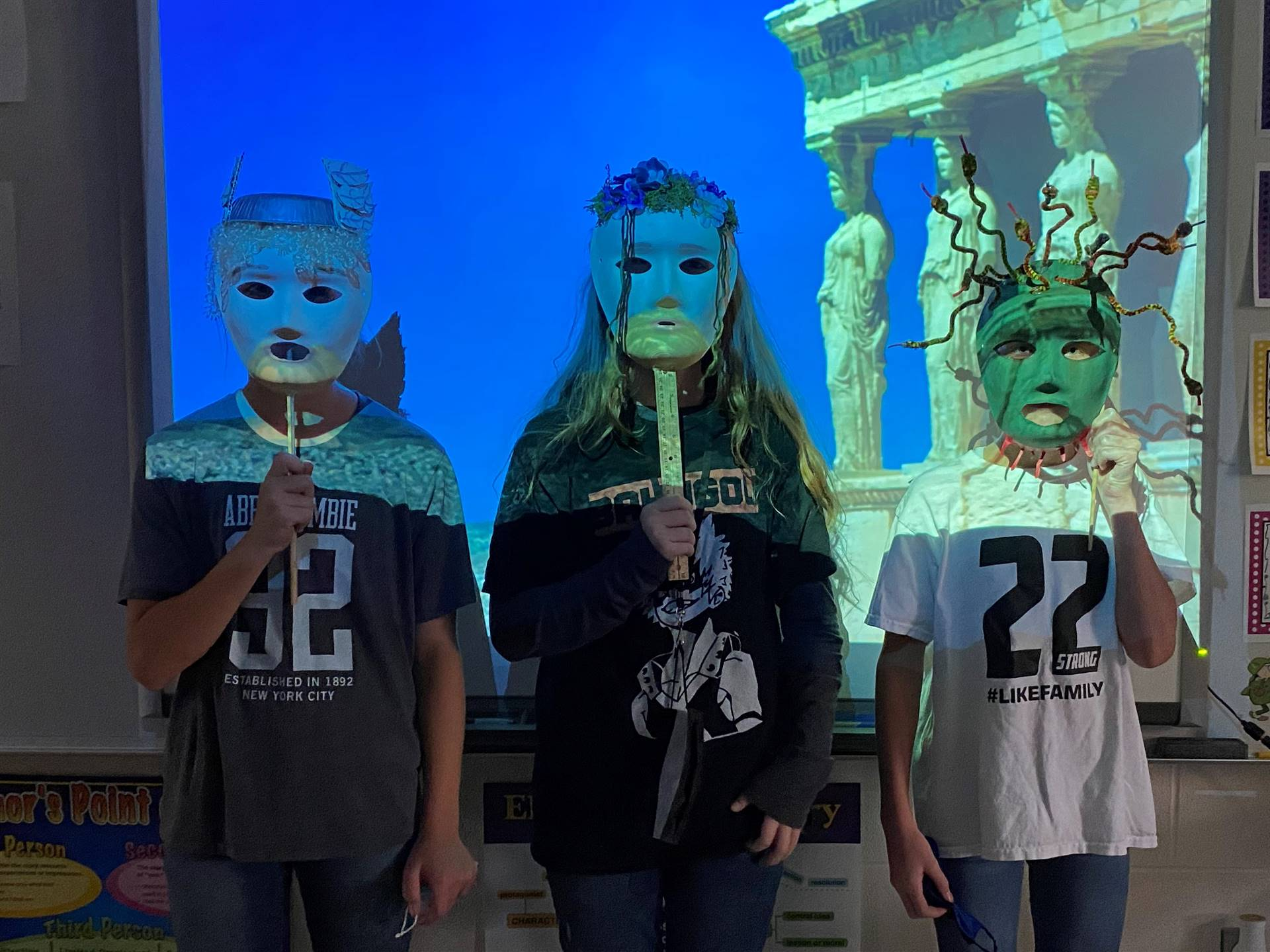 students wearing Greek masks